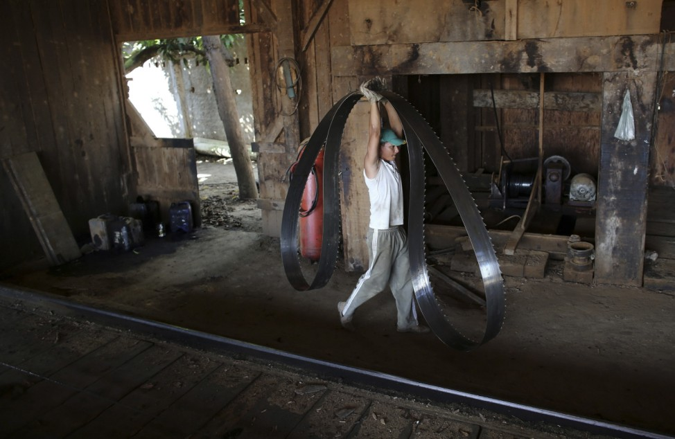 A worker carries a blade at a sawmill that processes trees illegally logged from the Amazon jungle near Morais Almeida