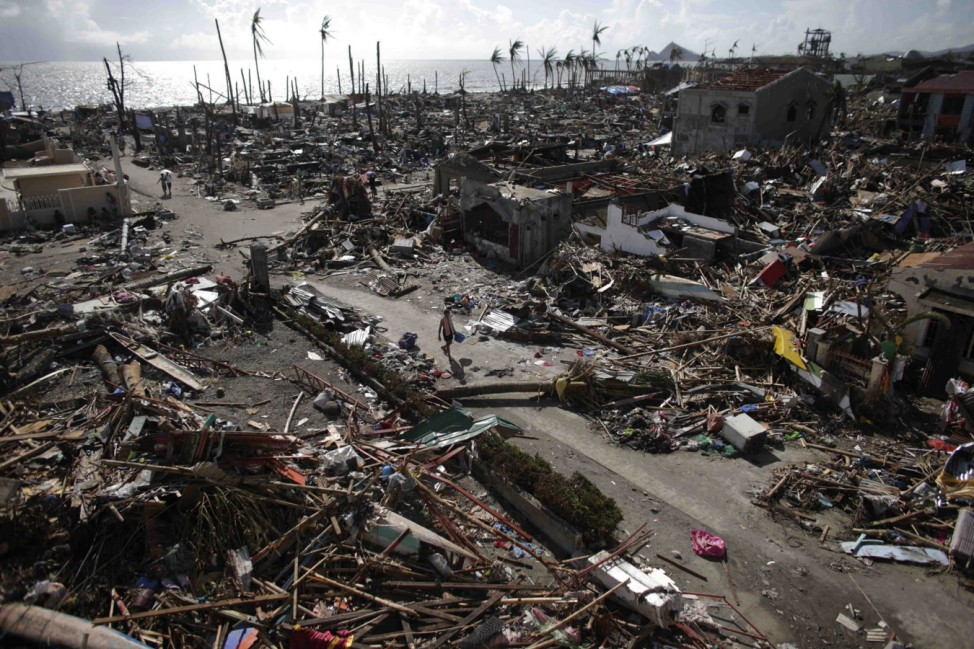 Residents walk in a village among houses destroyed by super Typhoon Haiyan in Tanauan