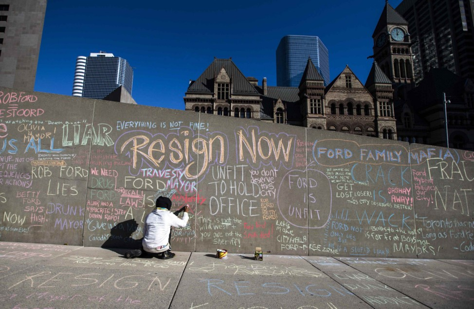 A woman writes a message on a wall where people are writing chalk messages about Toronto