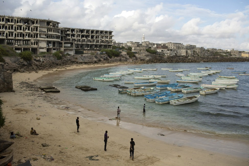 People stand and walk at a beach in the old port of Mogadishu
