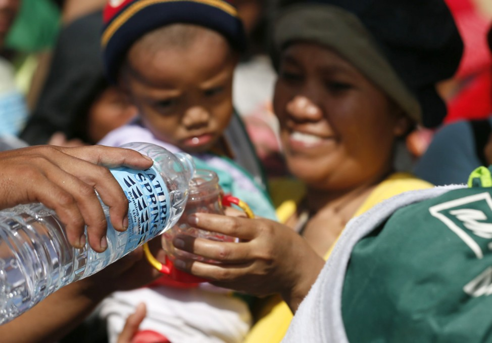 A woman receives water while waiting to be airlifted in the aftermath of super typhoon Haiyan at Tacloban