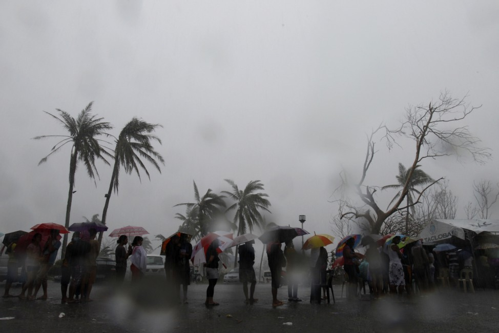 Survivors queue during a downpour to charge their mobile phones in the aftermath of super typhoon Haiyan in Tacloban