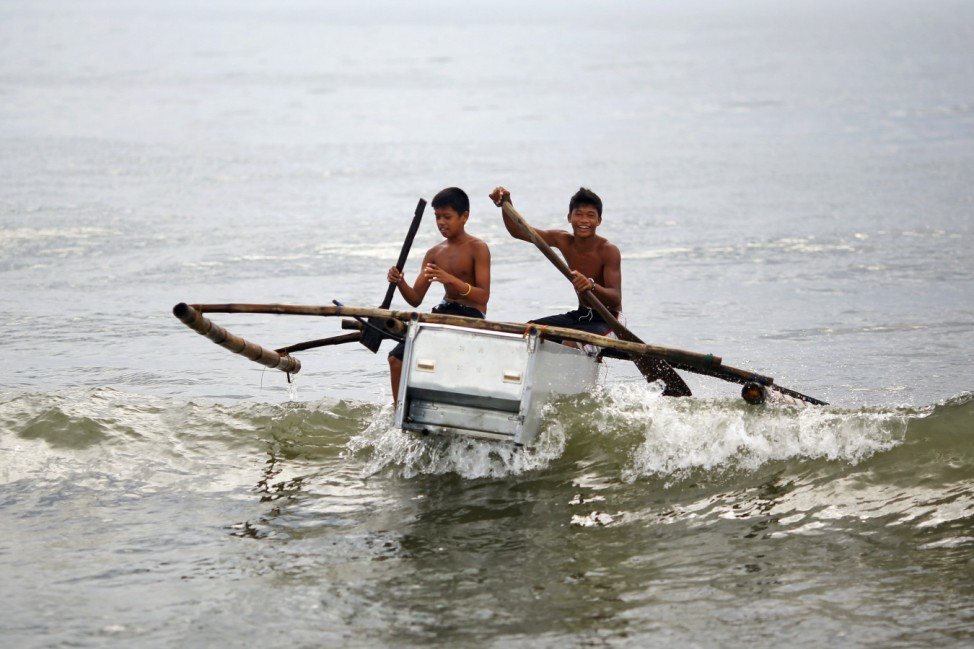 Boys maneuver their boat made of a broken fridge to the beach in Tanauan
