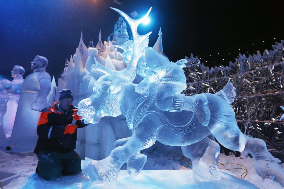 Sculptor Aseev of Russia carves a sculpture based on Disney's newest movie 'Frozen' at the Snow and Ice Sculpture Festival in Bruges