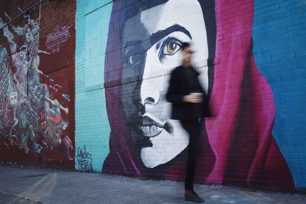 A man walks by a mural of Pakistani teenage activist Malala Yousafzai in the Bushwick section of the Borough of Brooklyn, New York