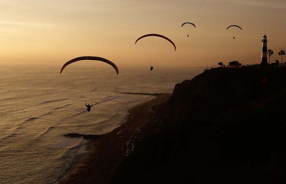 Paragliders fly in front of Lima's Miraflores district