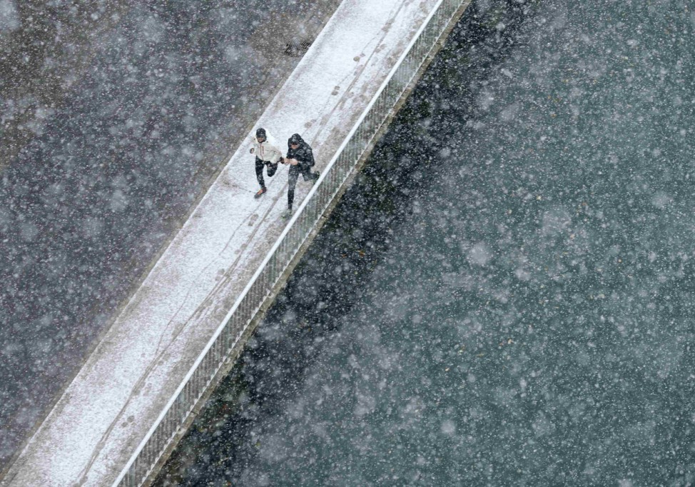 Two joggers run along the embankment of Aare river during the first snowfall in Bern