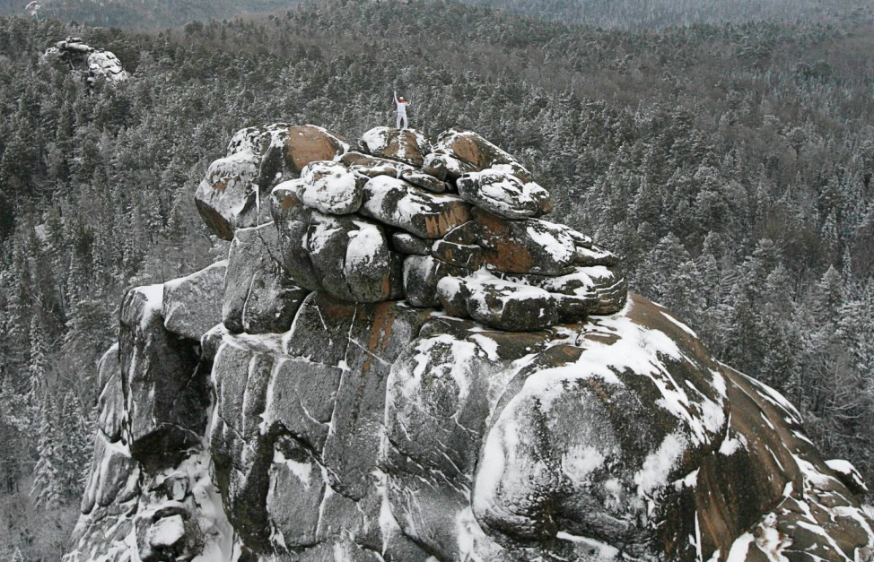 Russian alpinist Vladimir Gunko stands at the top of the rock named 'The First Stolb' (the First Pillar) outside Krasnoyarsk