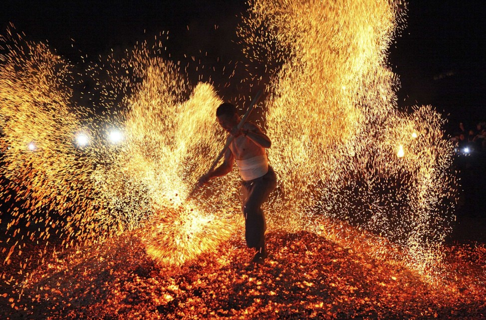 A man sweeps burning charcoal as he participates in the traditional ritual called 'Lianhuo', or 'fire walking', in Pan'an county
