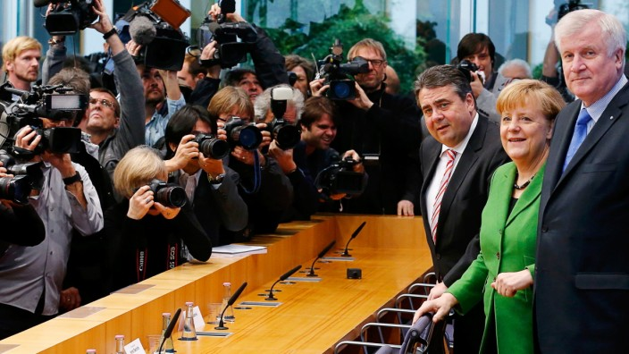 Party leaders German Chancellor Merkel of the CDU, Seehofer of the CSU and Gabriel of the SPD arrive for a news conference after signing a preliminary agreement, which has still to be approved by the members of the SPD, in the Bundespressekonferenz
