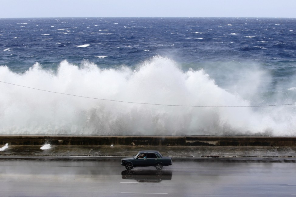 A car drives past a wave breaking on Havana's seafront boulevard 'El Malecon'
