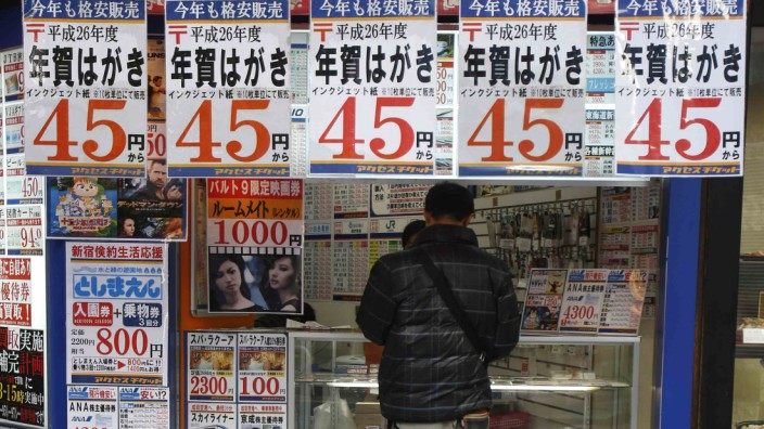 A man looks at the prices of tickets at a ticket shop in Tokyo