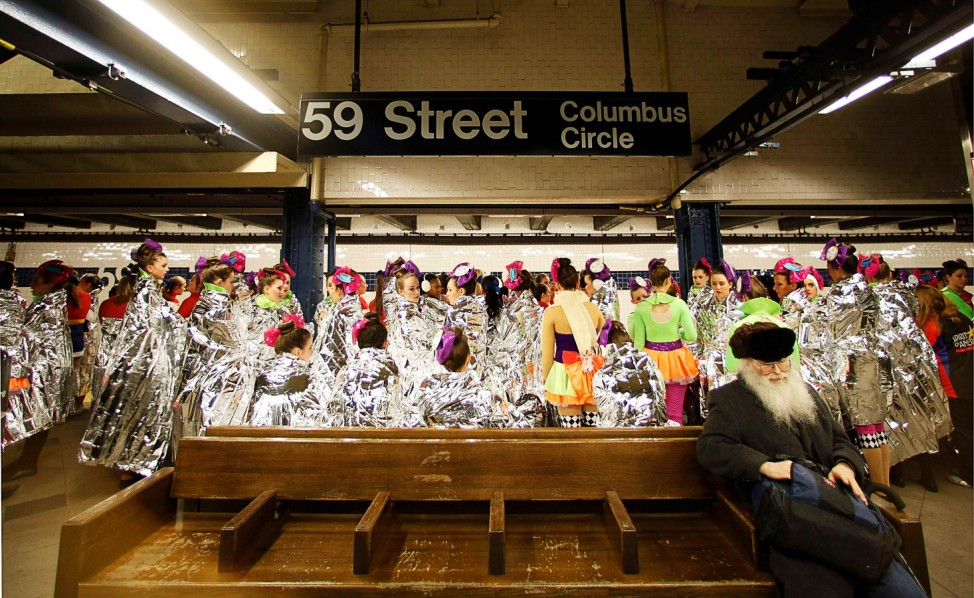 Performers in the 87th Macy's Thanksgiving Day Parade wait for a subway in New York