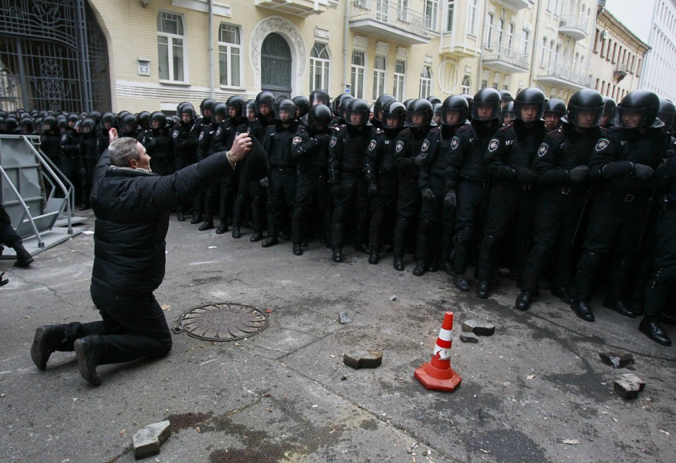 A man kneels down while riot police stand guard near the presidential administration building during a rally held by supporters of EU integration in Kiev
