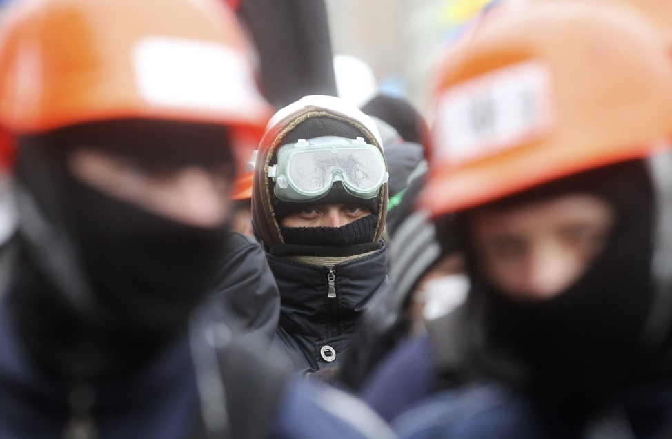 People wear helmets and masks as they attend a rally held by supporters of EU integration in Kiev