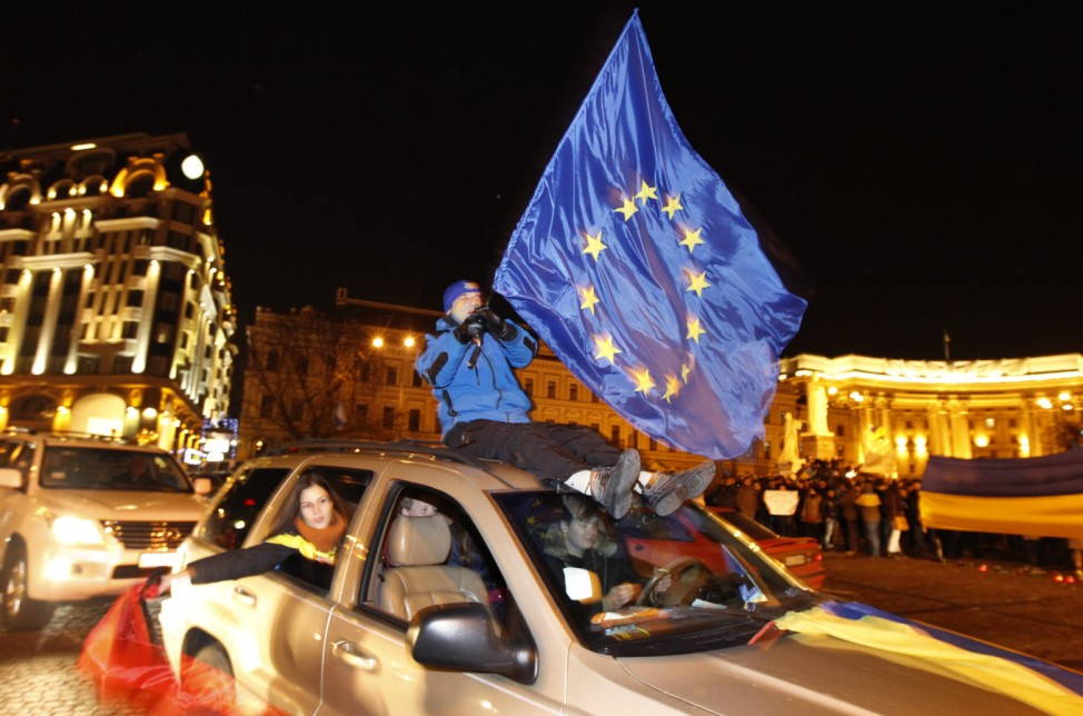 Protester waves an European Union flag from the top of a moving car in Kiev