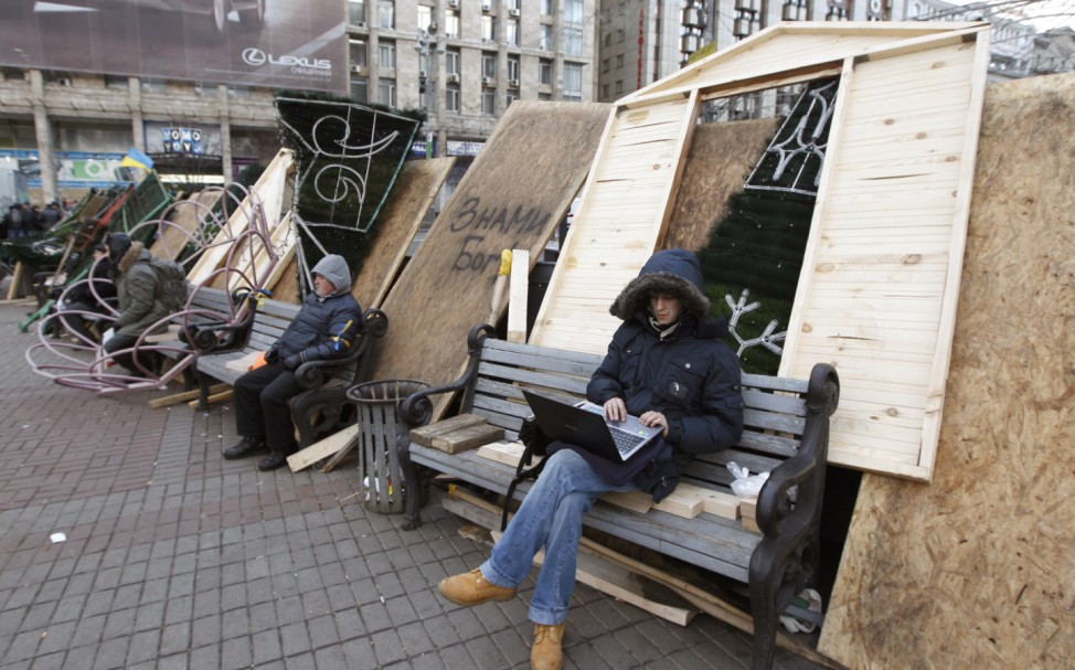 Protesters sit on barricades which blocked the main avenue in Kiev