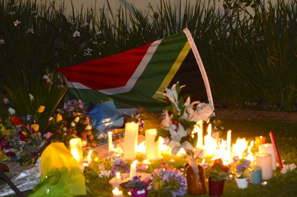 Candles burn in an impromptu shrine outside the residence of former South African President Nelson Mandela in Johannesburg