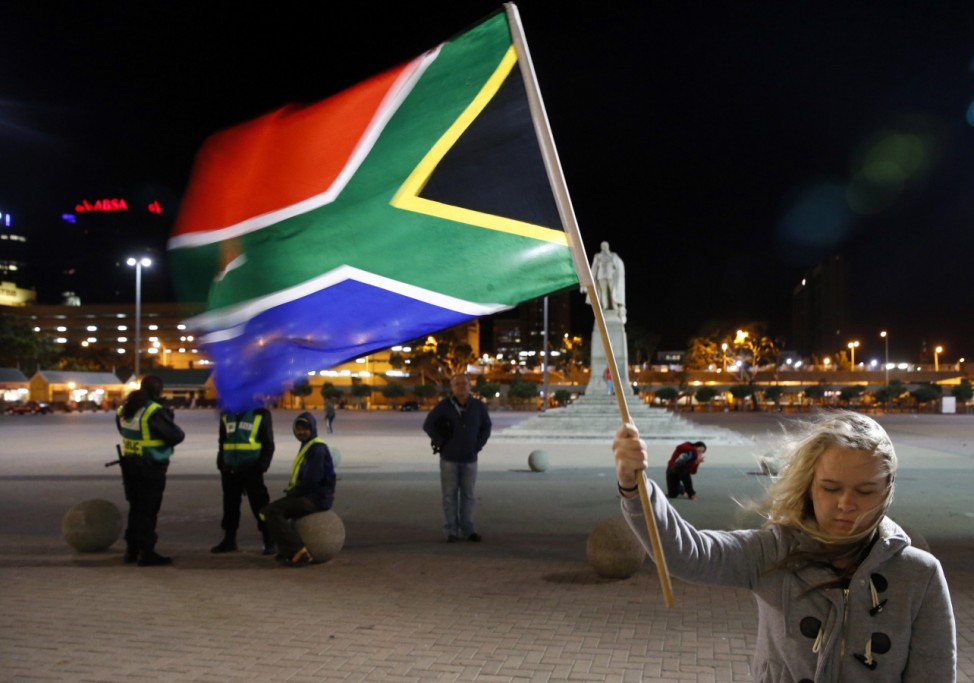 Girl holds a South African national flag as people mourn the death of former President Nelson Mandela outside Cape Town City Hall