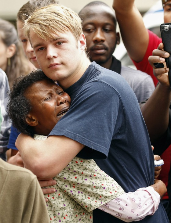 People comfort each other outside the residence of former South African President Nelson Mandela in Johannesburg