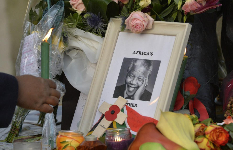 A woman places a candle next to tributes at a statue of former South African President Nelson Mandela in Parliament Square in London