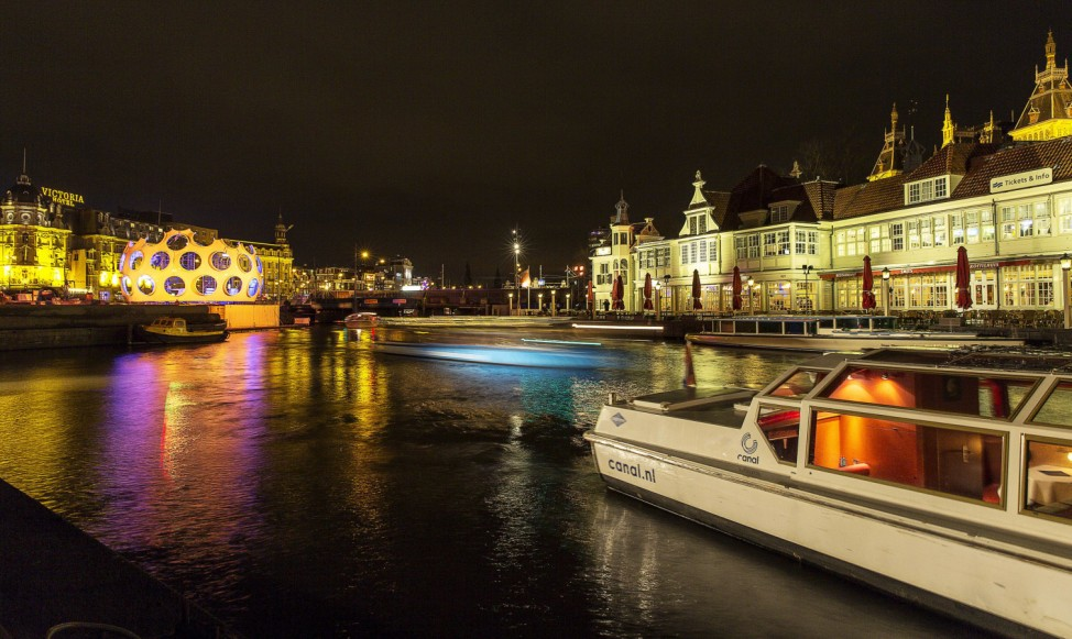 A tourist boat passes the orange 'Fly's Eye Dome' by Buckminster Fuller, which is on display as part of the Amsterdam Light Festival in Amsterdam