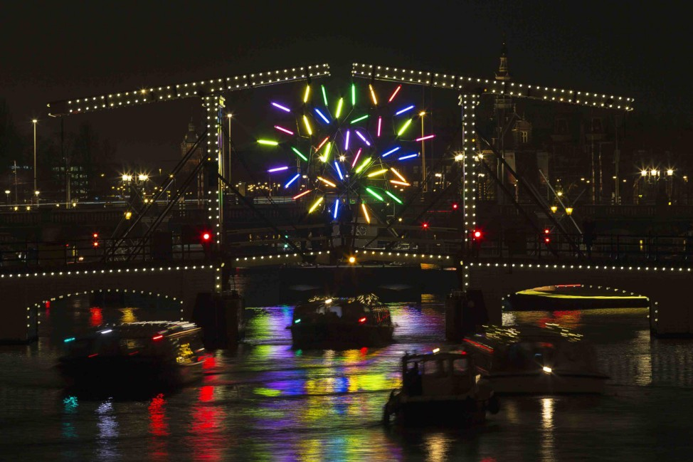 'Big Tree' by French artist Jacques Rival is seen through the Magere brug as part of the Amsterdam Light Festival in Amsterdam