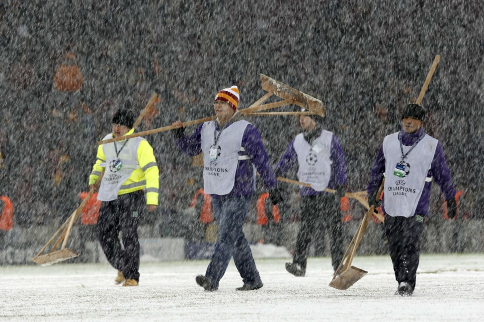 Workers rush to clean the snow from the pitch after the Champions League soccer match between Galatasaray and Juventus was paused for 20 minutes due heavy snowfall in Istanbul