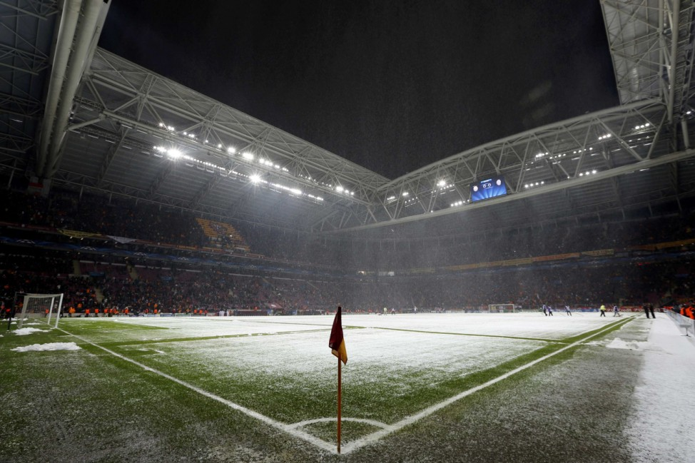 Workers clean the snow from the pitch after the Champions League soccer match between Galatasaray and Juventus was paused for 20 minutes due heavy snowfall in Istanbul