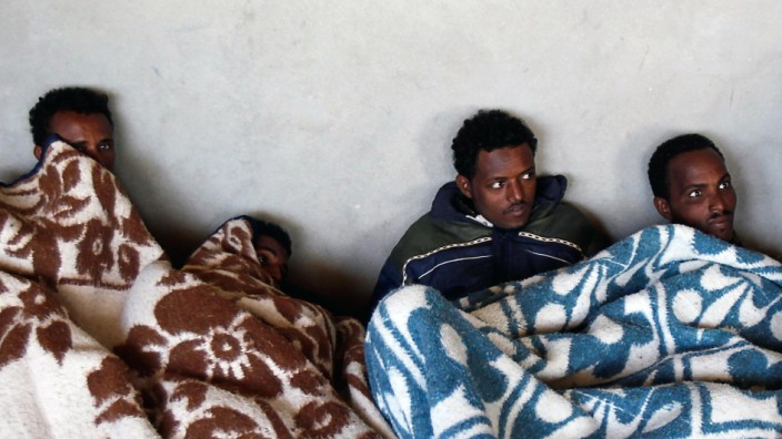 Migrants from Eritrea rest in a building, used to house people waiting to be smuggled into Israel, near the Egyptian-Israeli border in Sinai