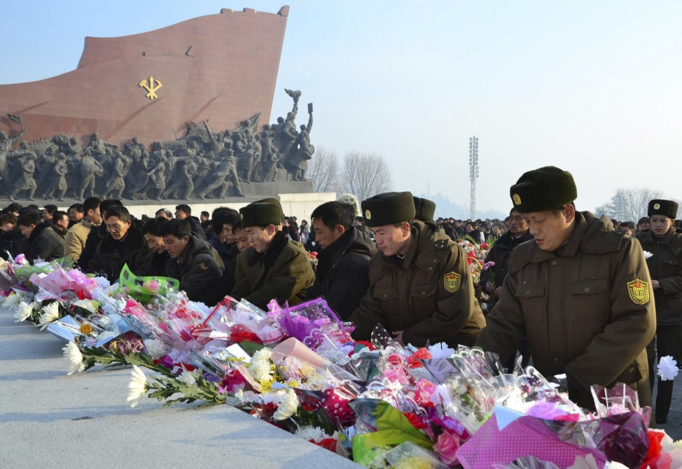 North Koreans offer flowers in front of statues of North Korea's founder Kim Il Sung and former leader Kim Jong Il at Mansudae hill in Pyongyang