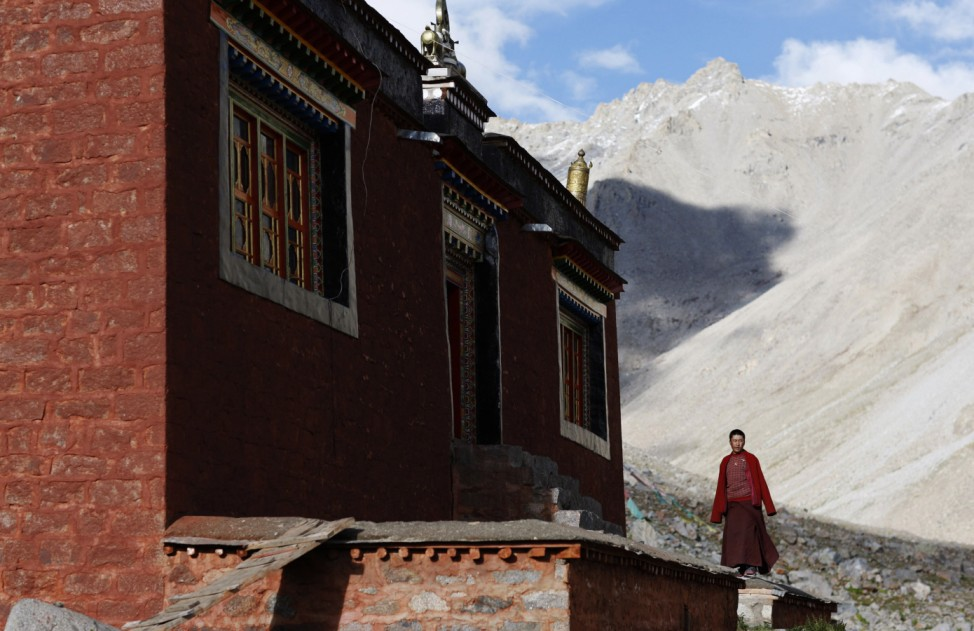 A Tibetan monk stands outside a temple near Mount Kailash in Ngari