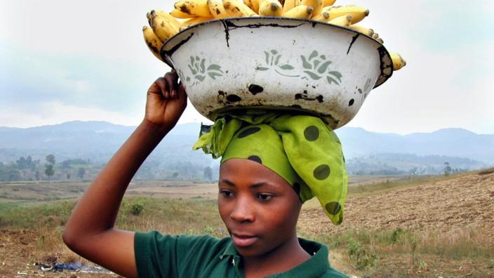 Frau transportiert Bananen in einer Schale auf dem Kopf