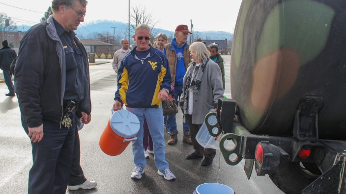 Residents line up for water at a water filling station at West Virginia State University, in Institute