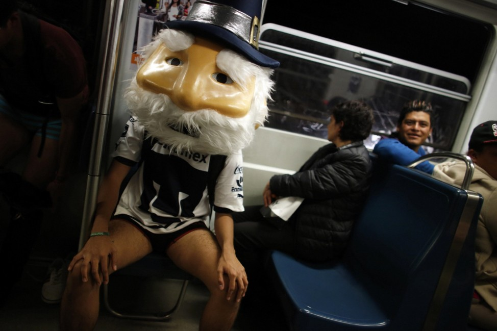 A man without pants and wearing a mask sits in a subway train during the 'No Pants Subway Ride' in Mexico City