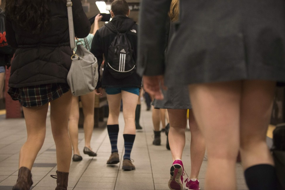 Passengers taking part in the annual No Pants Subway Ride in the Manhattan walk along a platform in the Manhattan borough of New York