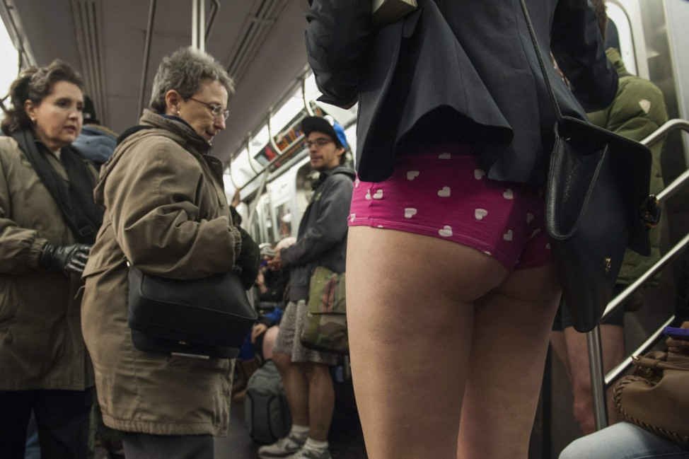 Passengers on a subway stand next to a girl dressed for the annual No Pants Subway Ride in the Manhattan borough of New York