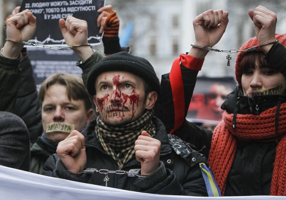 Pro-European integration supporters with taped mouths attend a rally against newly approved laws near the presidential administration in Kiev