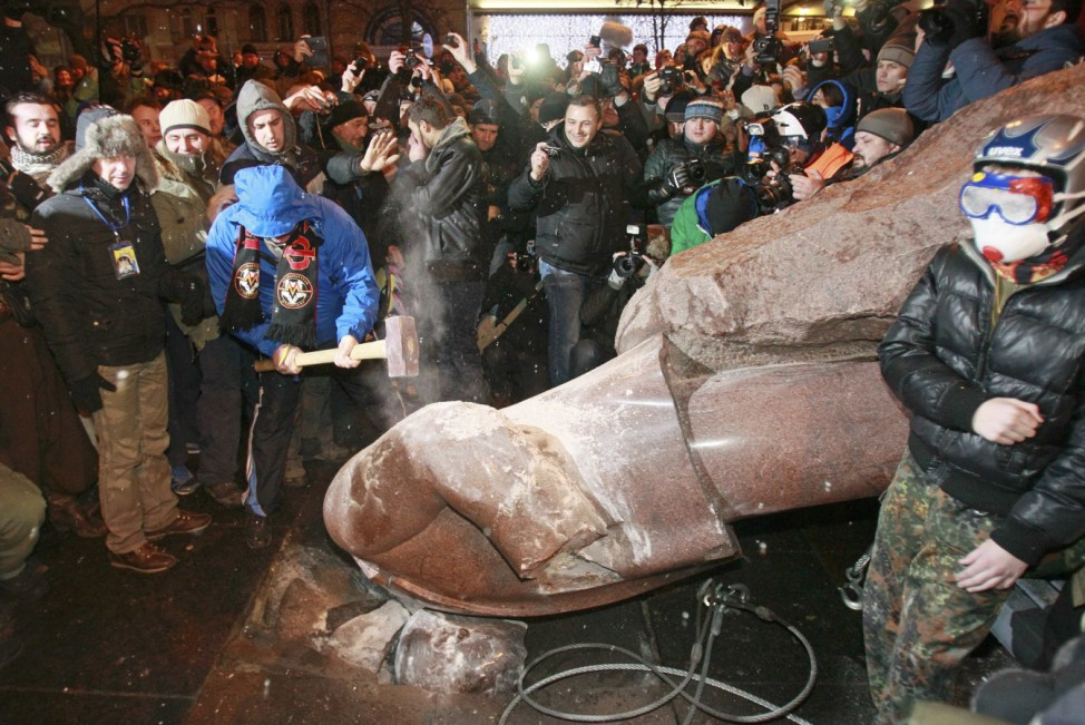 A man holds a sledgehammer as he smashes a statue of Soviet state founder Vladimir Lenin, which was toppled by protesters during a rally organized by supporters of EU integration in Kiev