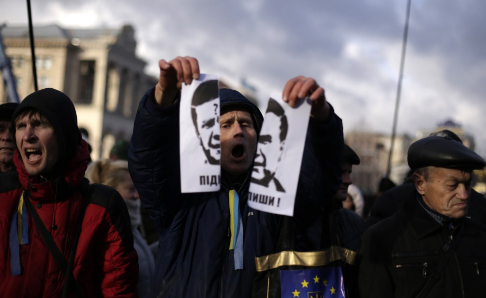 A protester tears a portrait of Ukraine's President Viktor Yanukovich during a demonstration in support of the EU integration in Kiev