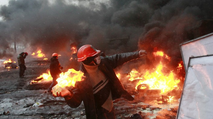 A pro-European protester throws a Molotov cocktail towards riot police near burning tyres during clashes in Kiev