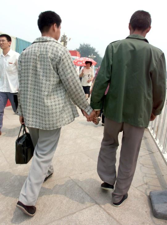 Zwei chinesische Männer halten Händchen.