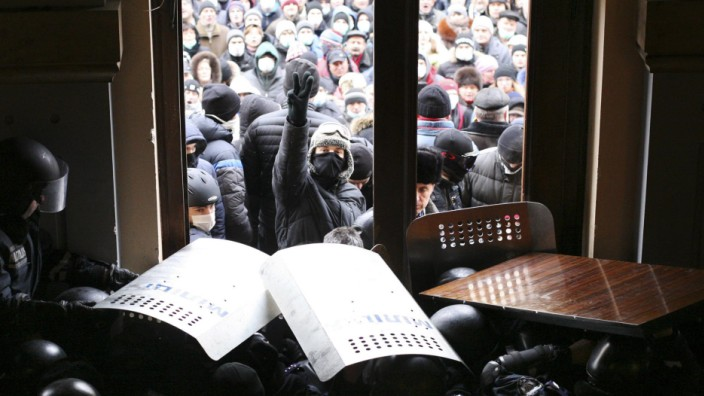 Anti-government protesters gather outside the regional administration headquarters as they attempt to take over during a rally, with Interior Ministry members standing guard inside the building, in the town of Chernivtsi
