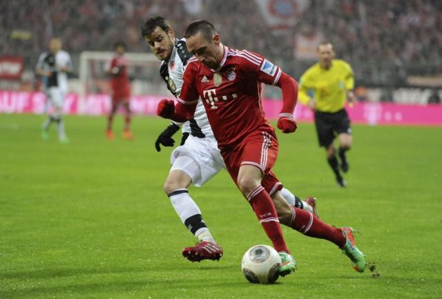 Bayern Munich's Franck Ribery is tackled by Eintracht Frankfurt's Tranquillo Barnetta during the German first division Bundesliga soccer match in Munich