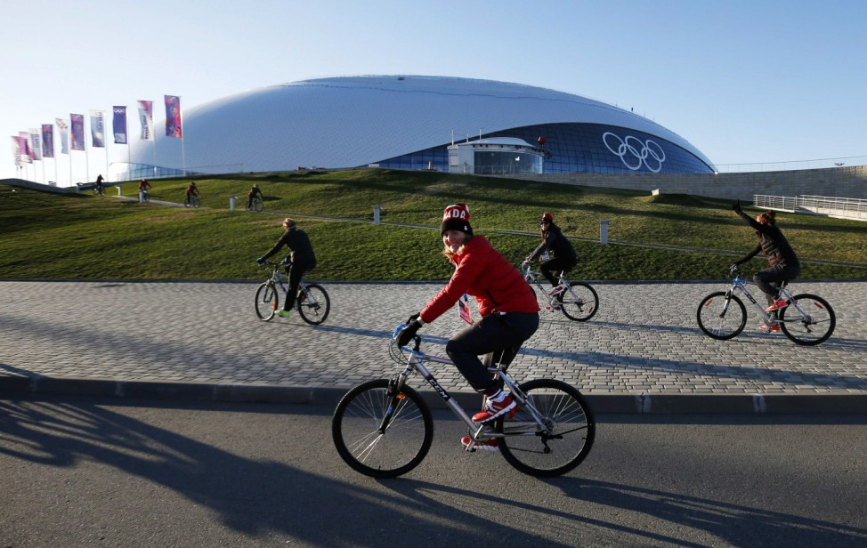 Team Canada women's ice hockey player and Canadian flag bearer Wickenheiser rides her bicycle with teammates in front of the Bolshoy Ice Dome