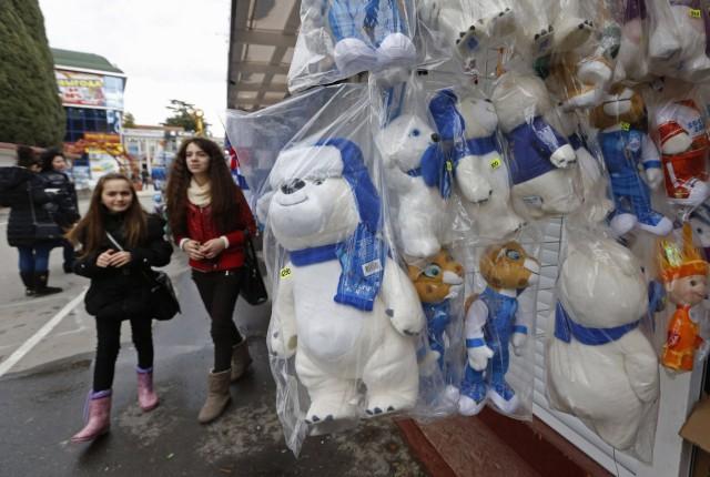 Russian girls walk near Sochi 2014 Winter Games' mascot soft toys in Sochi