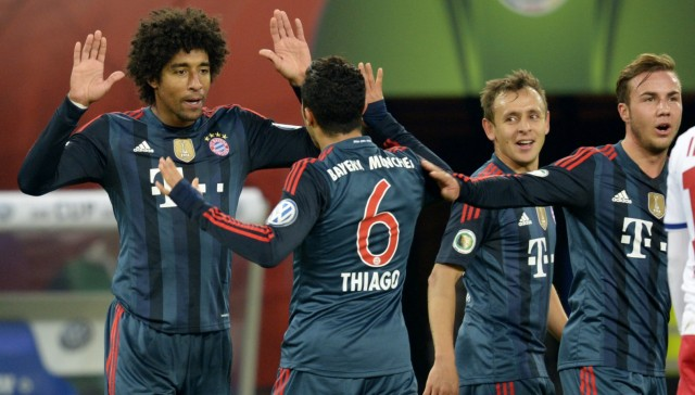 Bayern Munich's Dante is congratulated by his team mates after scoring during their quarter-final German soccer cup (DFB-Pokal) match in Hamburg