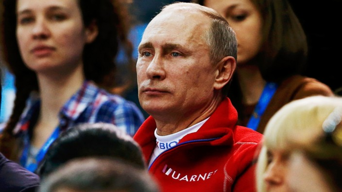 Russian President Vladimir Putin watches from the stands during the Team Ladies Free Skating Program at the Sochi 2014 Winter Olympics