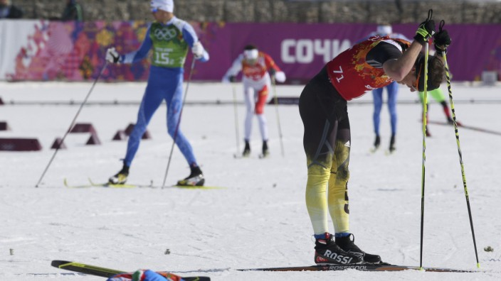 Italy's Noeckler lies on ground next to Germany's Filbrich during men's cross-country 4 x 10km relay event at 2014 Sochi Winter Olympics