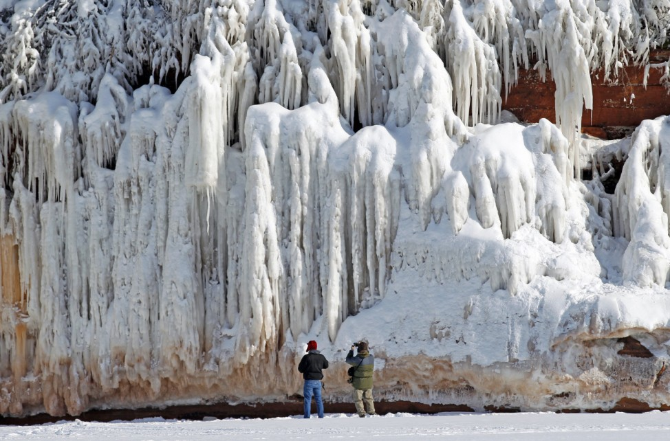 Sightseers look at a frozen rock face along the Apostle Islands National Lakeshore of Lake Superior